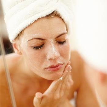 Women washing face with face scrub