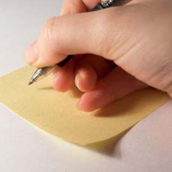 Person writing a note on a piece of paper